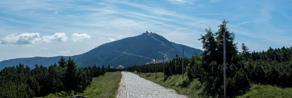 Stone path leading through mountain panorama with alpine vegetation to the highest peak Śnieżka in the Giant Mountains on the border of Poland and Czechia.
