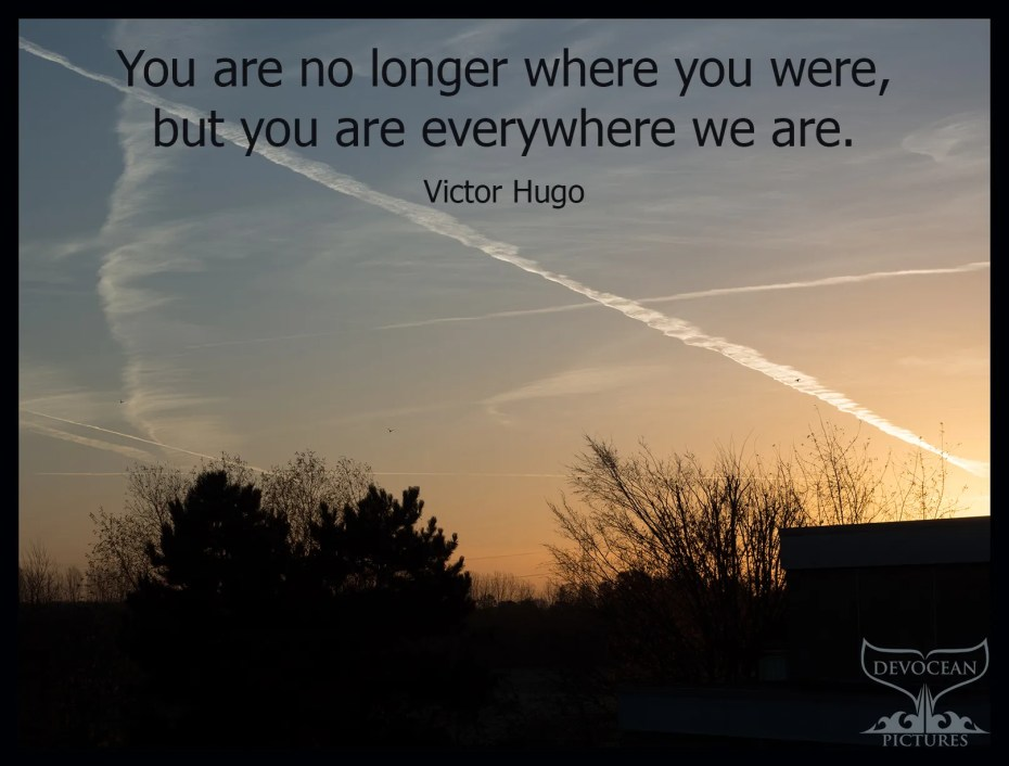 Postcard Warm regards from Devocean Pictures: Multicoloured sunrise with silhouettes and quote of Victor Hugo: You are no longer where you were, but you are everywhere we are.