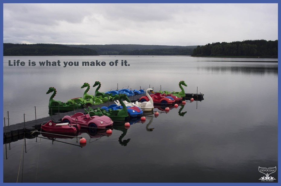 Postcard with warm regards from Devocean Pictures: Möhne See / Lake in Germany, summer 2015. The lake is smooth as glass, clouded sky and a pier with paddleboats in red and blue and 5 green dragons and one white swan waiting peacefully.