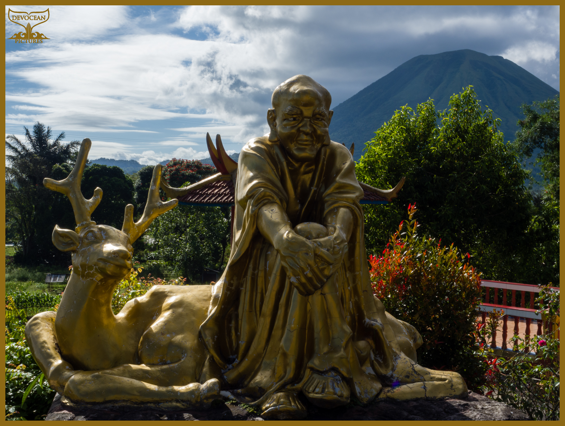 Statue in front of mount Lokon at Buddhist temple with pagoda and statue in Tomohon (Sulawesi, Indonesia). Postcard with warm regards from Devocean Pictures