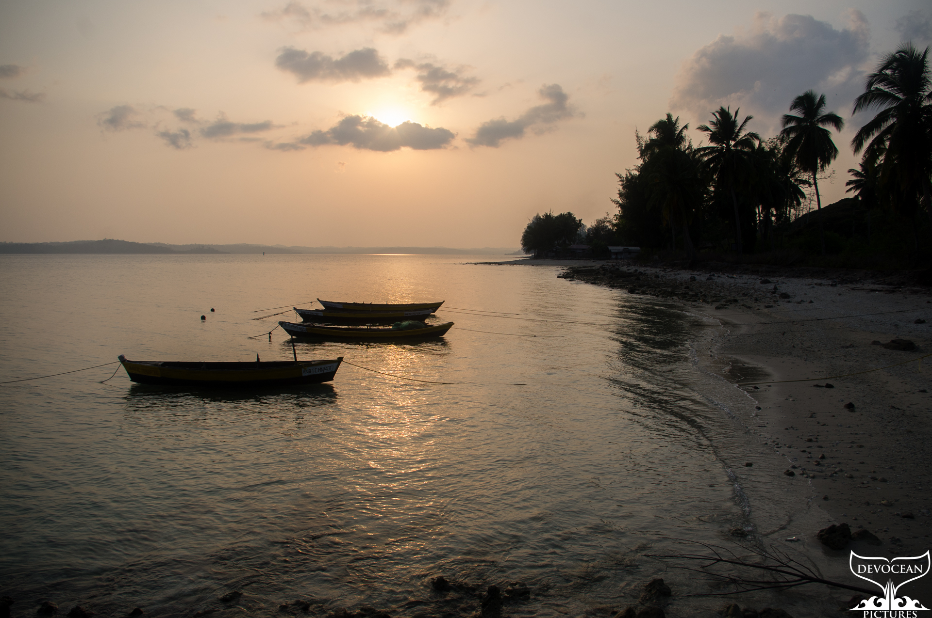 Sunset at South Beach on Long Island, Andamans, India: Three dungees are in the calm and shallow water in front of the beach that curves around with Silhouttes of trees and palms against mild orange yellow sky