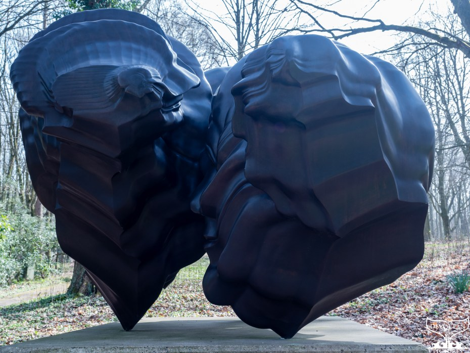 Another sculpture of Tony Cragg showing two heads facing each other and different layers of thoughts or words forming out of them standing in the woods on a concrete slap in the woods of the sculpture park Waldfrieden in Wuppertal, April 2021.