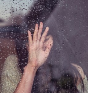woman with hand on rainy window