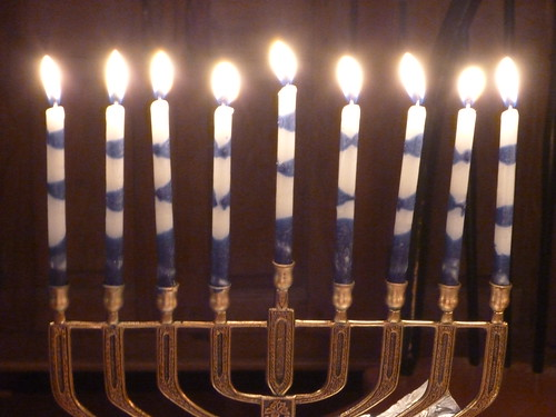 Close up of a Hanukkiah, all candles recently lit. The candles are made from striped blue and white wax