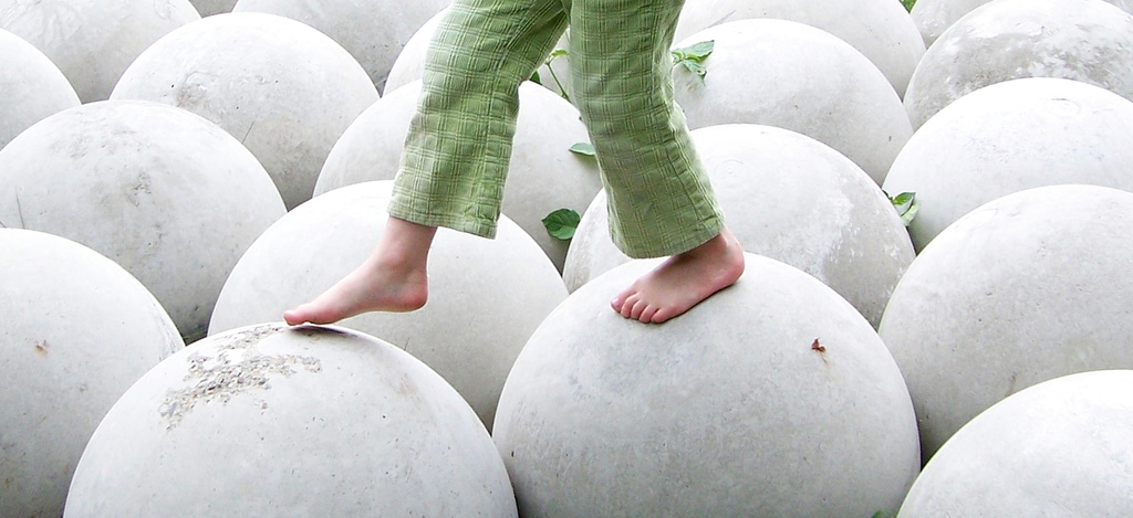 Photo person in green pants carefully walking on cement spheres