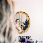 bride getting makeup done behind the scenes