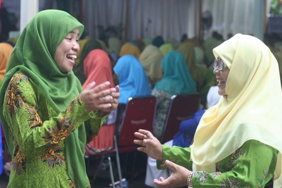 Acha (left) catches up with Ema, an Aisyiyah volunteer.