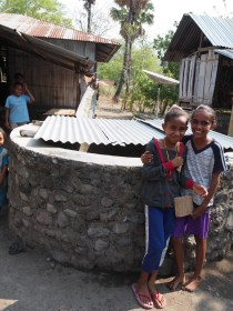 Girls stand next to an off-roof water tank constructed as part of an NTA program.