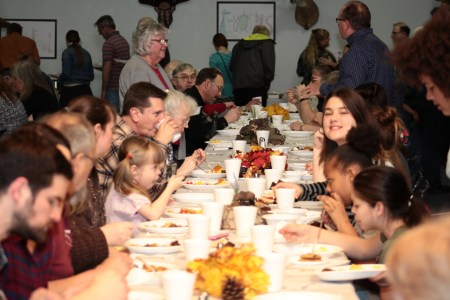 People of all ages gather around wild game dishes
