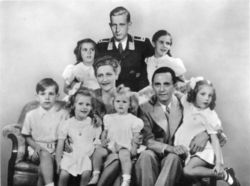 Portretul familiei Goebbels : in centru sunt Magda Goebbels si Joseph Goebbels, impreuna cu cei sase copii ai lor Helga, Hildegard, Helmut, Hedwig, Holdine si Heidrun. In spatele lor este Harald Quandt in uniforma de sergent aviator. German Federal Archives, sursa Wikipedia.
