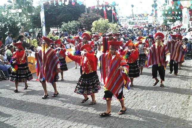 Jugendliche stellen auf einem Umzug den traditionellen Huayno-Tanz dar.