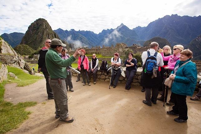 Eine viventura Gruppe lässt sich von einem erfahrenen Führer über den magischen Ort Machu Picchu aufklären.