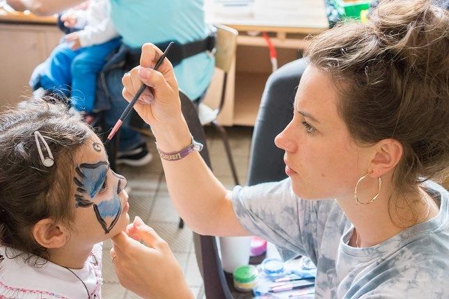 Eine Mitarbeiter schminkt das Gesicht eines kleinen Mädchens auf dem Sommerfest.