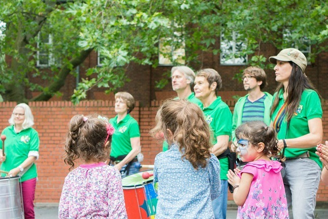 Kinder tanzen während die Berliner Sambagruppe Green Igelz trommelt beim viventura Sozialtag in Berlin.