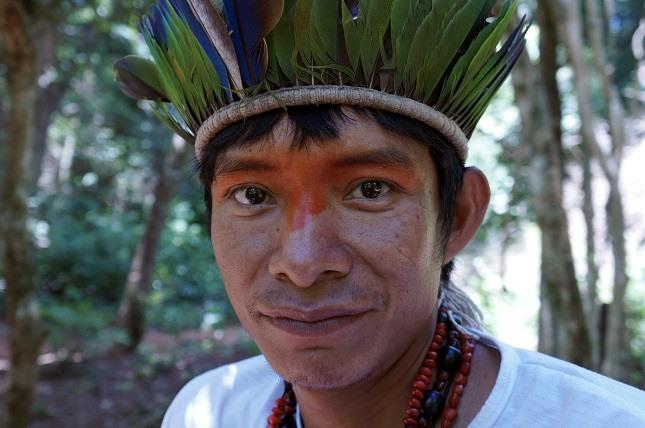 Indigene Völker im Amazonasgebiet: Ein Mitglied der Guarani mit einem Haarkranz voller grüner Federn und rot bemalten Augen schaut in die Kamera.