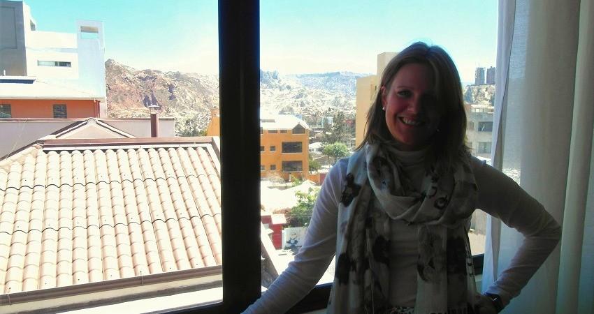 #viventurameets: Sozialprojekte in Bolivien - Hester steht im viventura Büro in La Paz am Fenster, im Hintergrund die Berge.