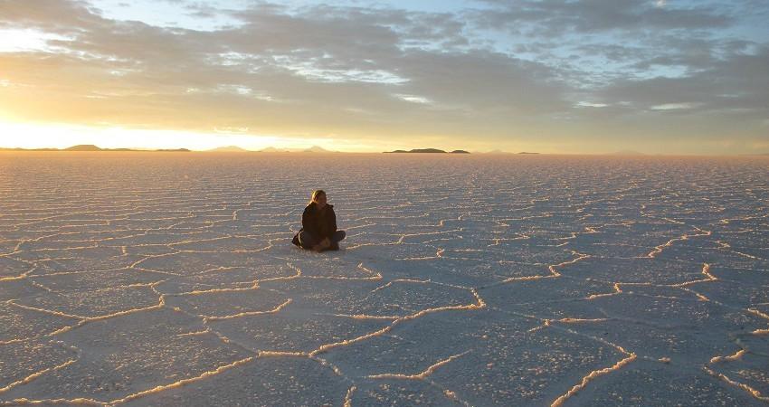 Praktikum in La Paz: Von hier aus hat man die Chance die ganze Vielfalt Boliviens zu erkunden. Wie zum beispiel am Sal de Uyuni. Hier sitzt Sarah im Schneidesitz und schaut in den Sonnenuntergang.
