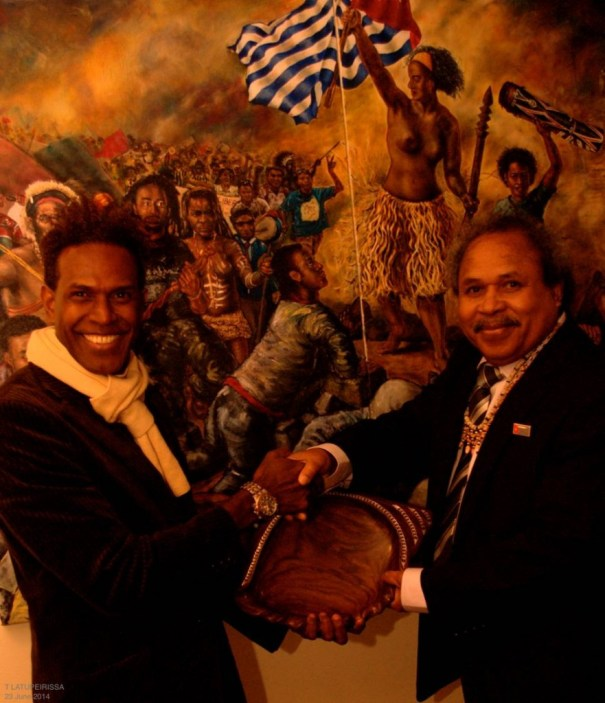 Foreign Affairs Minister Jacob Rumbiak, with Matt Gale (Solomon Islands Association in Victoria) in front of 'Liberty Papua leading the people (after Delacroix)' by Peter Woods 2011