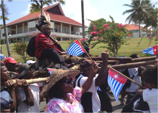 Benny Wenda riding the pig past Parliament House