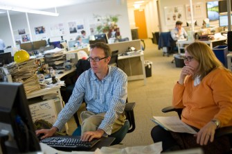 Denver Post online producer Kevin Hamm and reporter Noelle Phillips collaborate on a story Jan. 12, 2016 in the newsroom. Patrick Traylor, The Denver Post