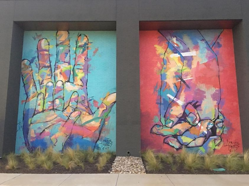 Two large murals by Adrian Torres of hands painted on the side of an office building