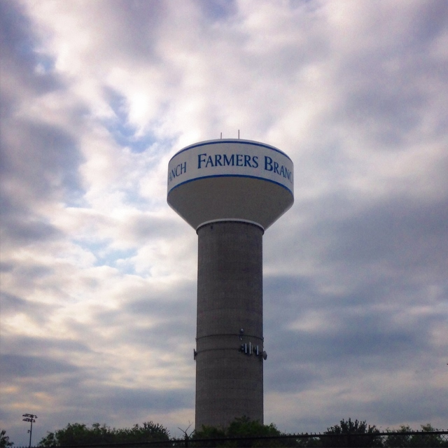 A ground-level view of a watertower for Farmers Branch, Texas