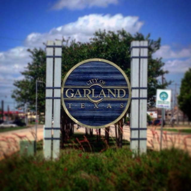 The large blue circular sign welcoming people to Garland, Texas.