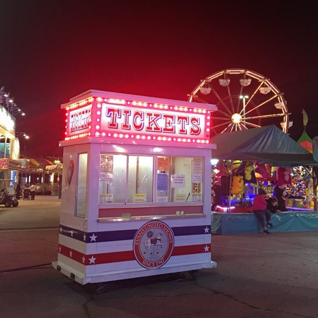 A night shot of a carnival ticket booth with a ferris wheel in the background.