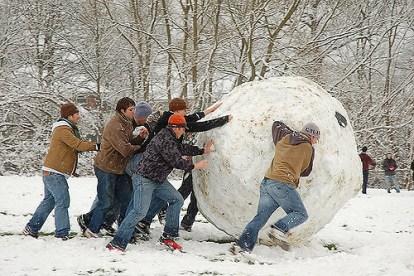 Men rolling a snowball.