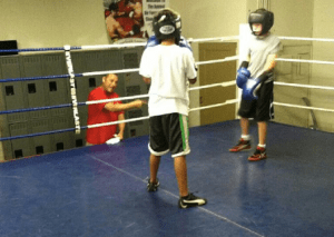 Coach Rivas instructs two amateur boxers
