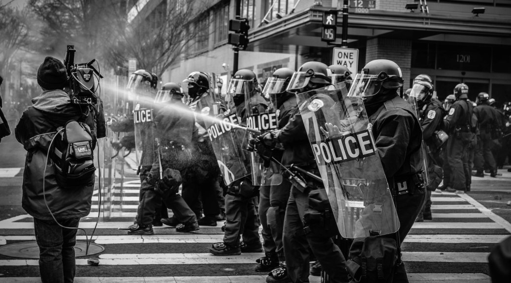 police marching in riot gear spray protestors with tear gas - for just world hypothesis article