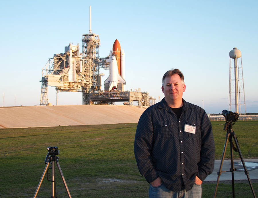 Chase Clark posing with Space Shuttle Endeavour perched atop historic Launchpad 39A in the background.