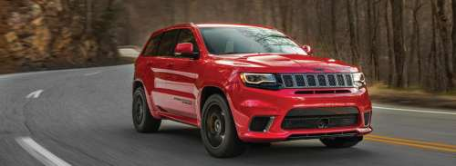 small resolution of a red 2018 jeep grand cherokee driving down an open road