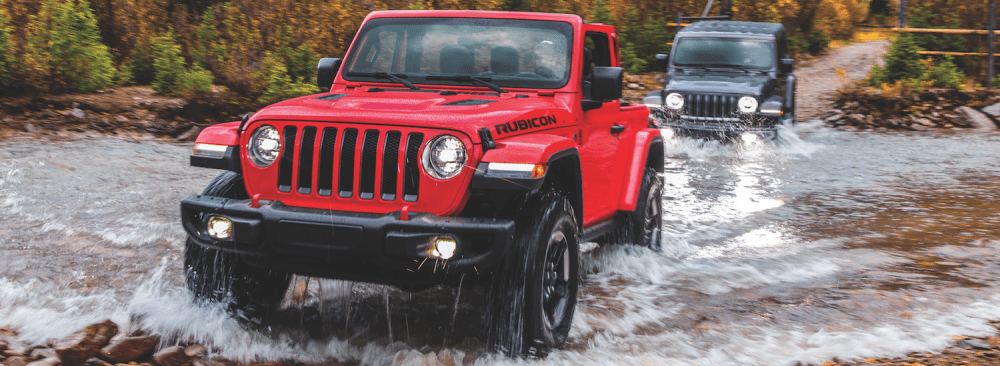 medium resolution of two jeep wranglers offroading through a creek