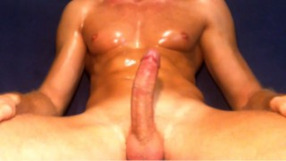 Oiled muscular man masturbating on the couch and cumming