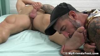 Stud flexes before masturbating while having his feet licked