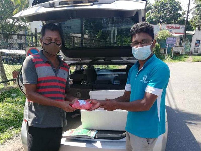 Vikasith and Gemunu loading car with supplies