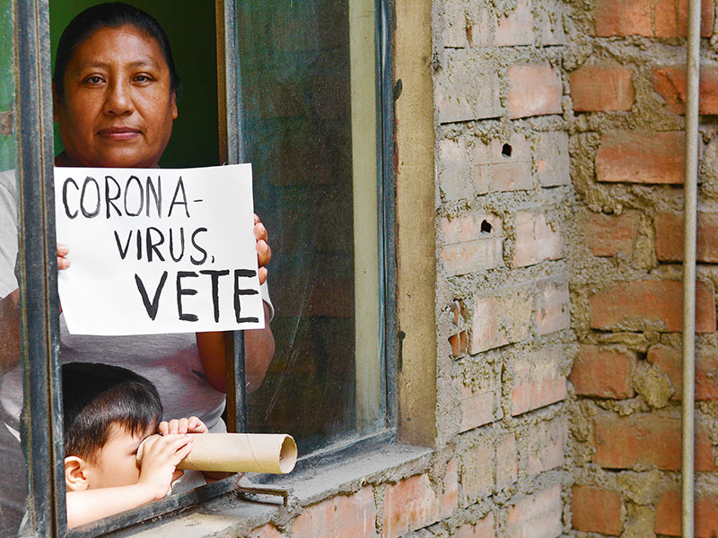 "Women holding coronavirus ""go-away"" sign in Spanish"