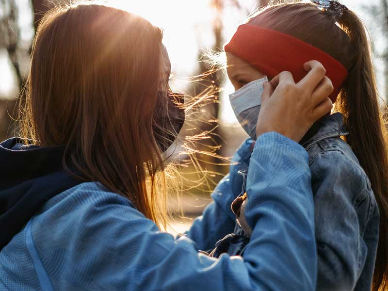 A girl with a child is standing on the road in a protective medical mask