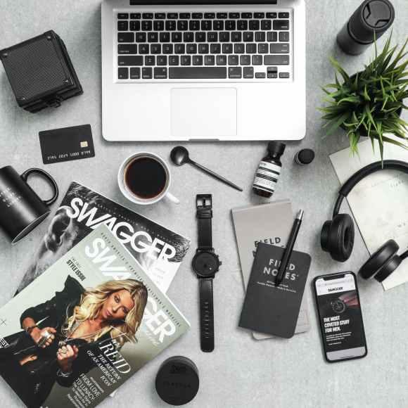 macbook pro beside dslr camera and mug