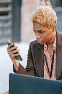 serious black businesswoman reading message on smartphone