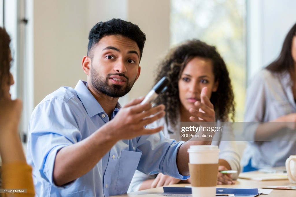 A young male design professional sits at a conference table with coworkers and gestures as he shares his ideas.