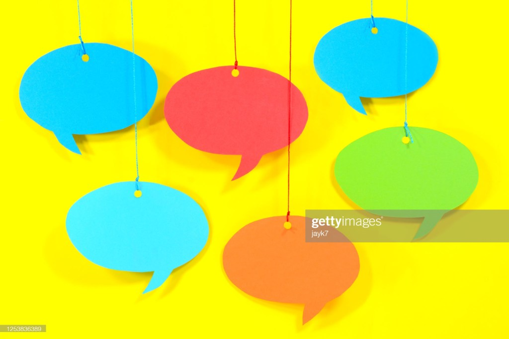 Multicolored speech bubble hanging from a string.