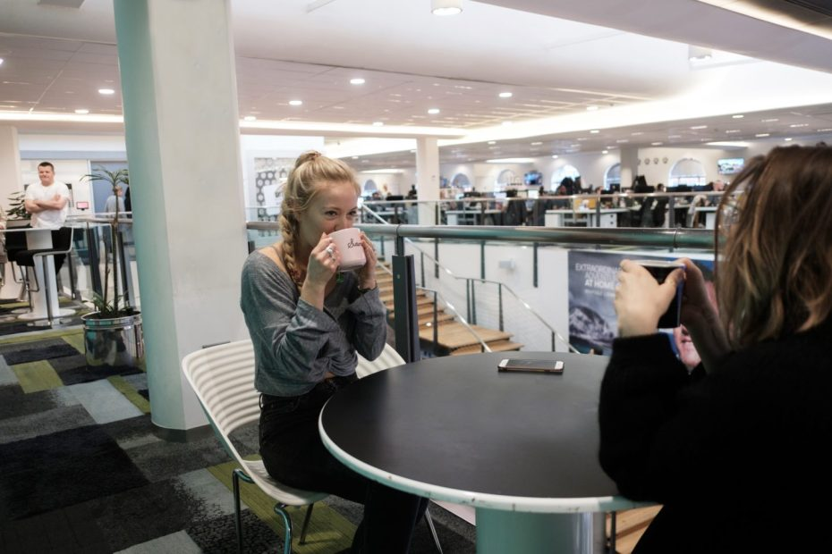 A blond white woman drinks from a cup of tea at a table in an open plan office.