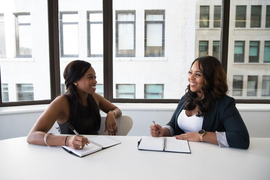 Two black women chat in a meeting by a large window.