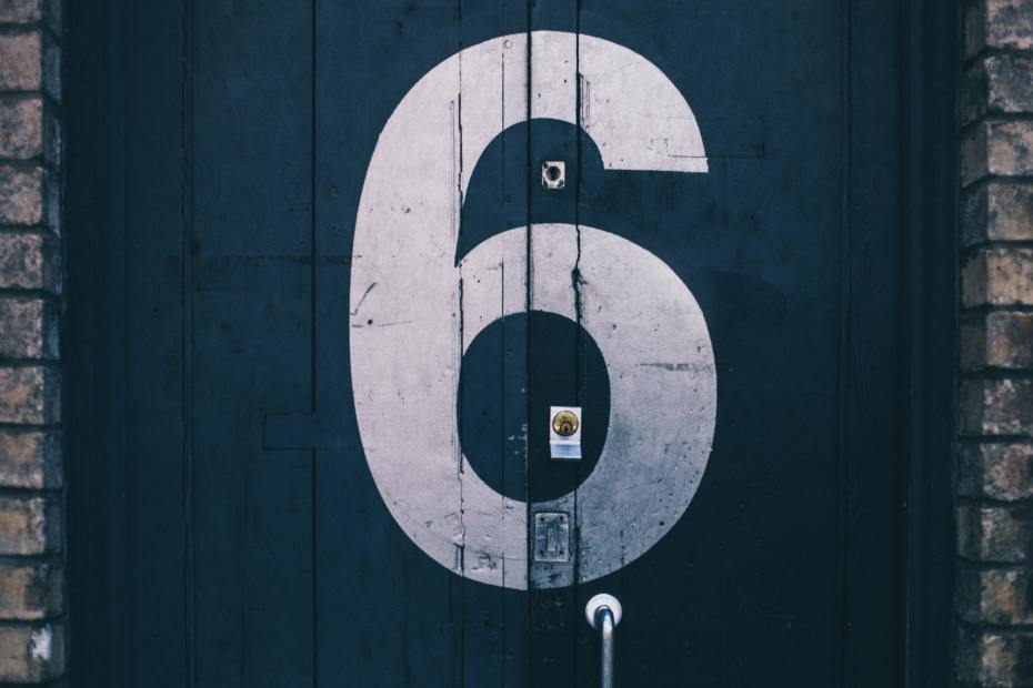 The number 6 painted in white on a blue door