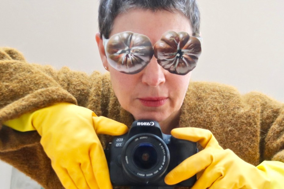 A white woman with short, grey hair wears yellow rubber gloves and holds a SLR camera. She has silver flowers on her eyes.