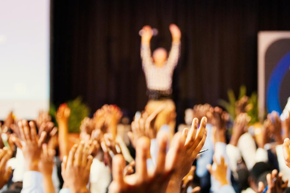 A crowd with hands in the air. In the distance a person stands with both hands in the air on a stage.