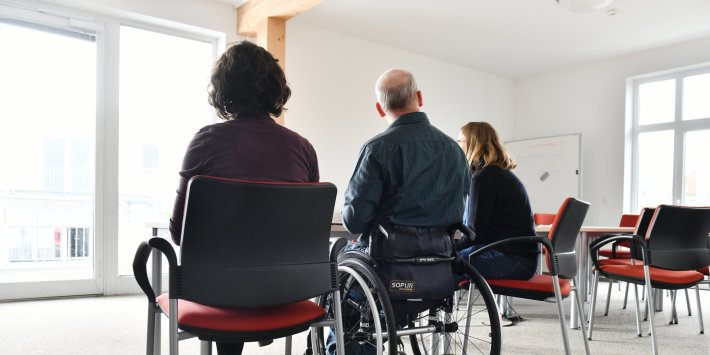 A man in a wheelchair and two women in chairs face a window