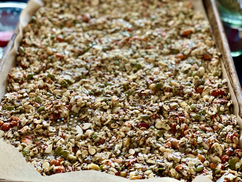 Granola ingredients laid out on a sheet pan before baking